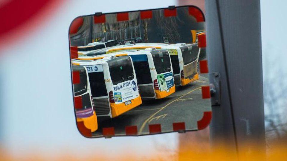 Busse stehen auf dem Betriebshof und spiegeln sich dabei in einem Verkehrs-Spiegel. Foto: Andreas Arnold/dpa/Archivbild
