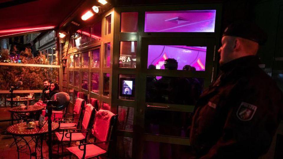 Ein Polizist steht während einer Razzia in einer Shisha-Bar. Foto: Bernd Thissen/Archiv