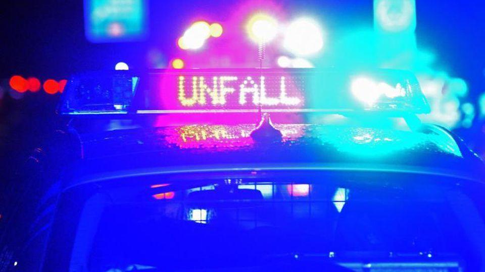 """das Blaulicht und der LED- Schriftzug """"Unfall"""" auf dem nassen Dach eines Polizestreifenwagens. Foto: Stefan Puchner/dpa/Archivbild"""