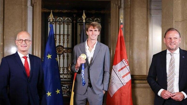 Bürgermeister Peter Tschentscher (SPD, l-r), Tennis-Olympiasieger Alexander Zverev und Andy Grote (SPD), Innen- und Sportsenator. Foto: Christian Charisius/dpa