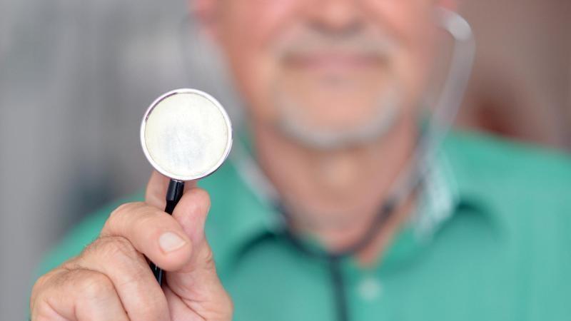 Ein Arzt hält ein Stethoskop nach oben. Foto: picture alliance /dpa/Illustration