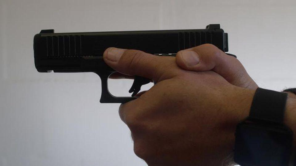 Ein Mann hält eine Schusswaffe in der Hand. Foto: Klaus-Dietmar Gabbert/zb/dpa/Archivbild