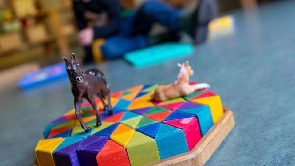 Ein Kind spielt in einem Kindergarten auf dem Boden. Foto: Monika Skolimowska/dpa-Zentralbild/dpa/Symbolbild