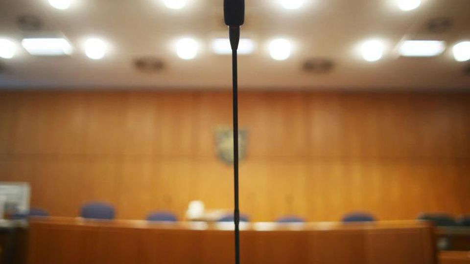 Am Platz des Zeugentisches steht in einem Verhandlungssaal im Landgericht ein Mikrofon. Foto: Fredrik von Erichsen/dpa/Archivbild