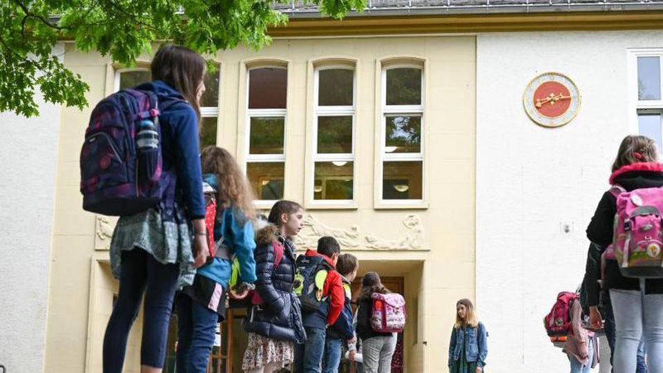 Schülerinnen und Schüler stehen vor dem Unterricht mit Abstand auf dem Schulhof. Foto: Arne Dedert/dpa/Archiv/Symbolbild