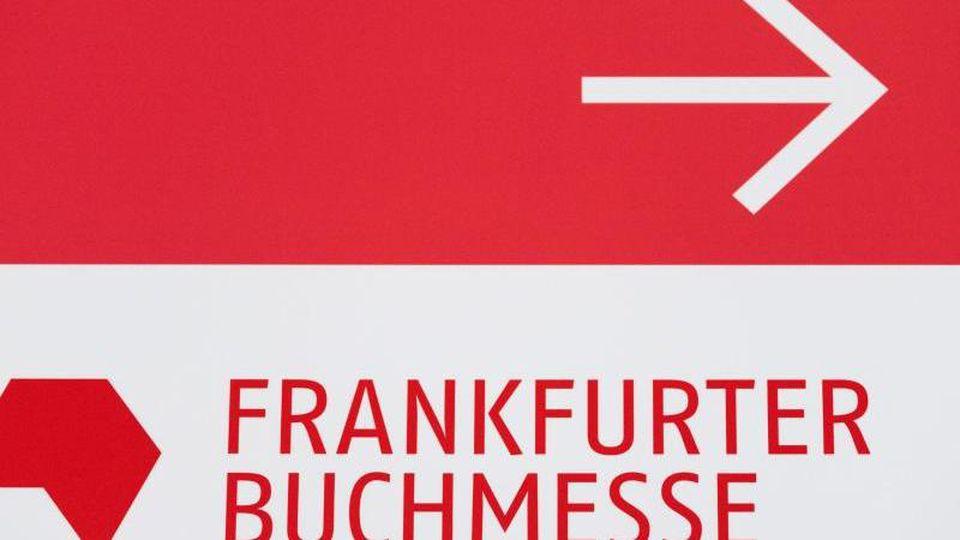 Das Logo der Frankfurter Buchmesse auf einem Wegweiser auf dem Messegelände. Foto: Silas Stein/dpa/Archivbild