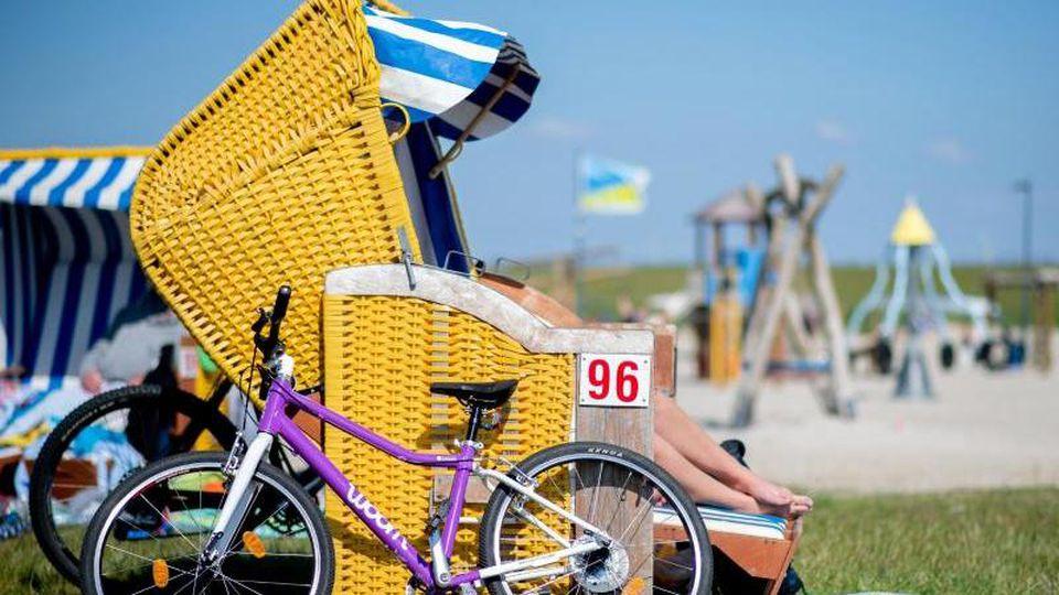 Ein Fahrrad steht an einem Strandkorb am Friesenstrand. Foto: Hauke-Christian Dittrich/dpa/Symbolbild