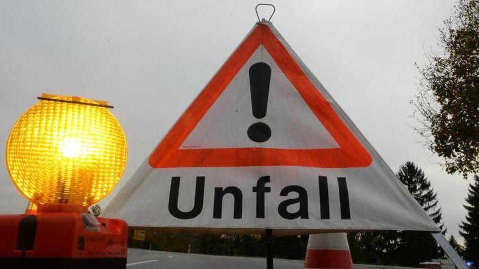 """Ein Warndreieck mit der Aufschrift """"Unfall"""" steht auf der Straße. Foto: Patrick Seeger/Archiv"""