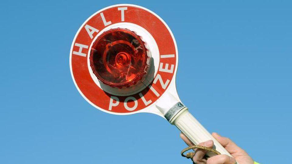 """Eine Kelle mit der Aufschrift: """"Halt Polizei"""" wird hoch gehalten. Foto: Ralf Hirschberger/dpa-Zentralbild/dpa/Archivbild"""