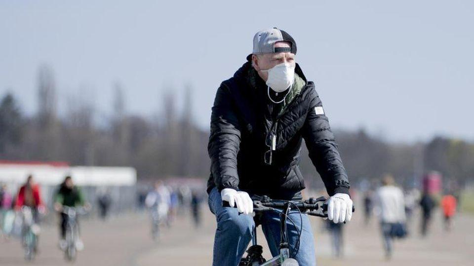 Ein Mann mit Schutzmaske und Handschuhen fährt auf dem Tempelhofer Feld Fahrrad. Foto: Christoph Soeder/dpa
