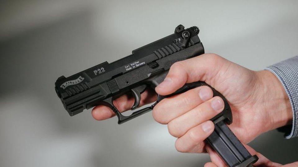 """Hände laden eine Schreckschuss-Pistole """"Walther P22"""" mit einem Magazin. Foto: Oliver Killig/zb/dpa/Archivbild"""