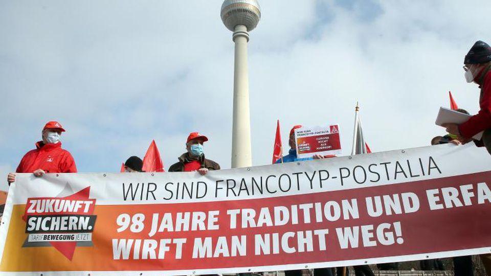 Menschen nehmen an einer Demo der IG Metall gegen den Abbau von Arbeitsplätzen teil. Foto: Wolfgang Kumm/dpa