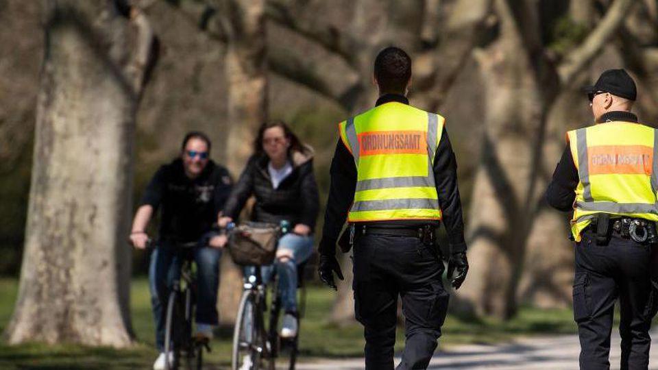 Mitarbeiter des Ordnungsamts kontrollieren in einem Park die Einhaltung der Schutzmaßnahmen. Foto: Marius Becker/dpa/Archivbild