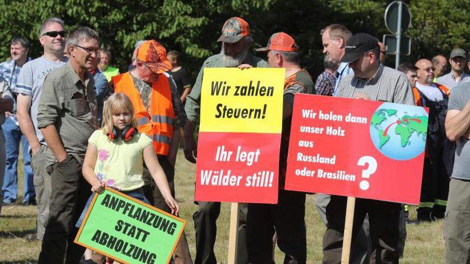 Teilnehmer einer Protestaktion gegen Waldstilllegung stehen auf einer Wiese vor einem betroffenen Waldstück. Foto: Bodo Schackow