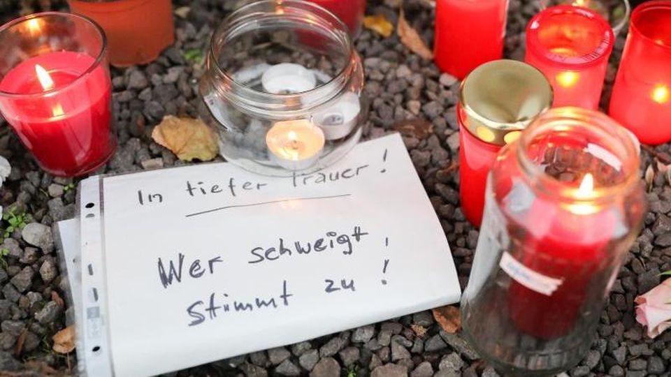"""Kerzen, Blumen und ein Zettel mit der Aufschrift """"In tiefer Trauer Wer schweigt stimmt zu!"""" liegen vor einem Dönerladen. Foto: Jan Woitas/zb/dpa"""