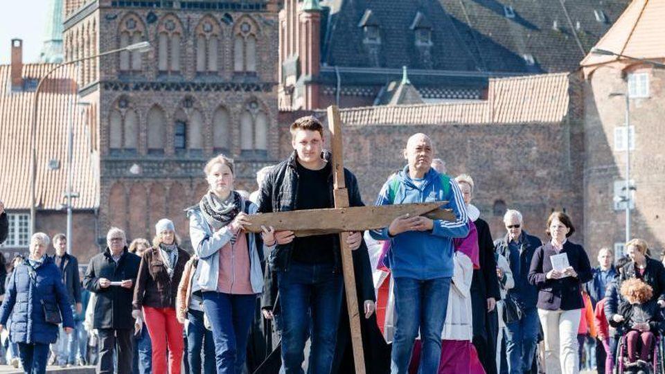 Katholiken und Protestanten gehen auf einem ökumenischen Kreuzweg gemeinsam mit einem Kreuz durch die Altstadt. Foto: Markus Scholz