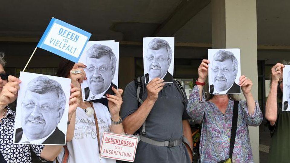 Demonstranten halten sich Porträts des erschossenen Walter Lübckes vor das Gesicht. Foto: Uwe Zucchi