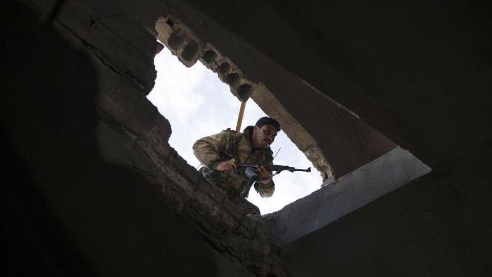Ein Kämpfer der von den USA unterstützten Syrischen Demokratischen Kräfte schaut im Kampf gegen die Terrorgruppe IS in ein Gebäude im syrischen Baghus. Foto: Felipe Dana/AP