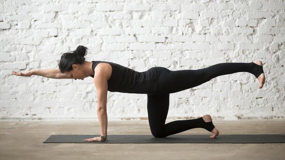 Junge Frau macht Yoga-Übung im Vierfüßlerstand auf einer Yogamatte