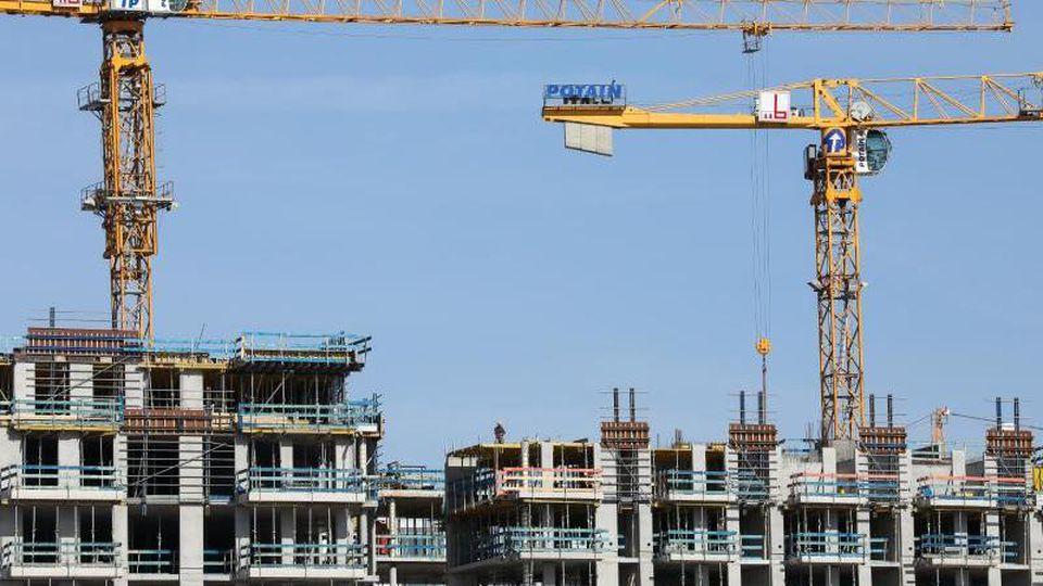 Kräne stehen auf einer Baustelle für mehrstöckige Wohnhäuser. Foto: Christian Charisius/dpa/Symbolbild