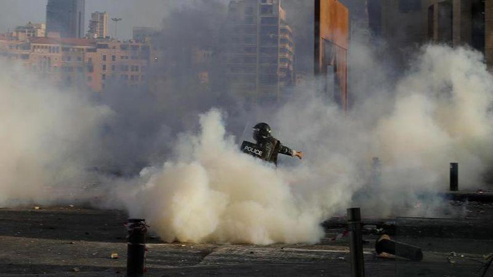Ein Bereitschaftspolizist stößt bei einem Protest mit Demonstranten zusammen. Foto: Hassan Ammar/AP/dpa