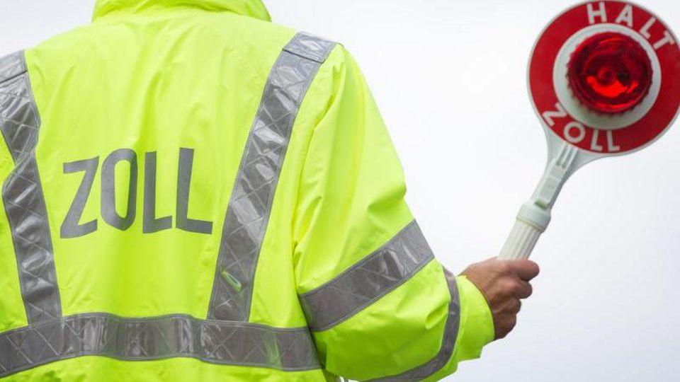 Ein Zollbeamter bittet darum, anzuhalten. Foto: Friso Gentsch/Archivbild