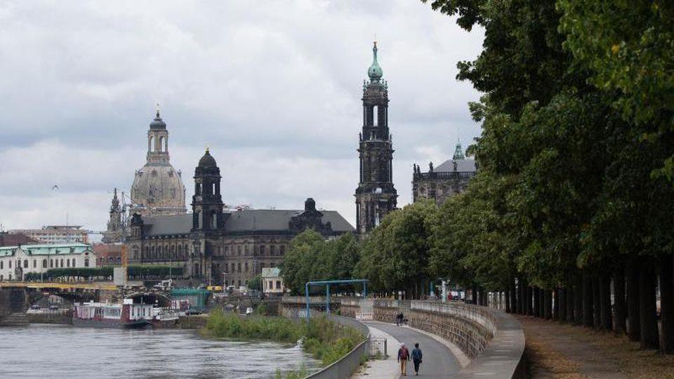 Passanten gehen am Ufer der Elbe vor der Kulisse der Altstadt entlang. Foto: Sebastian Kahnert/dpa-Zentralbild/ZB
