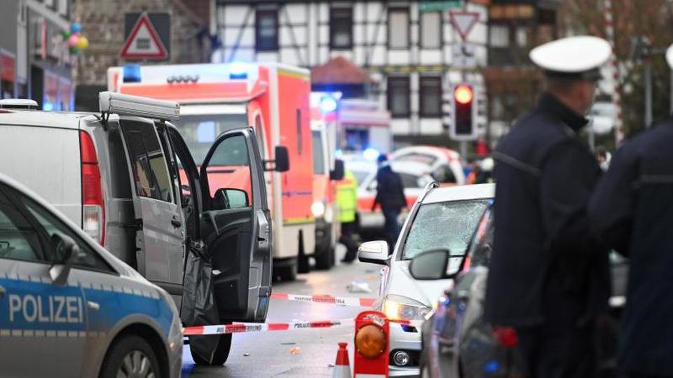 Polizeibeamte stehen an der Stelle, an der ein Auto in einen Rosenmontagsumzug gefahren ist. Foto: Uwe Zucchi/dpa