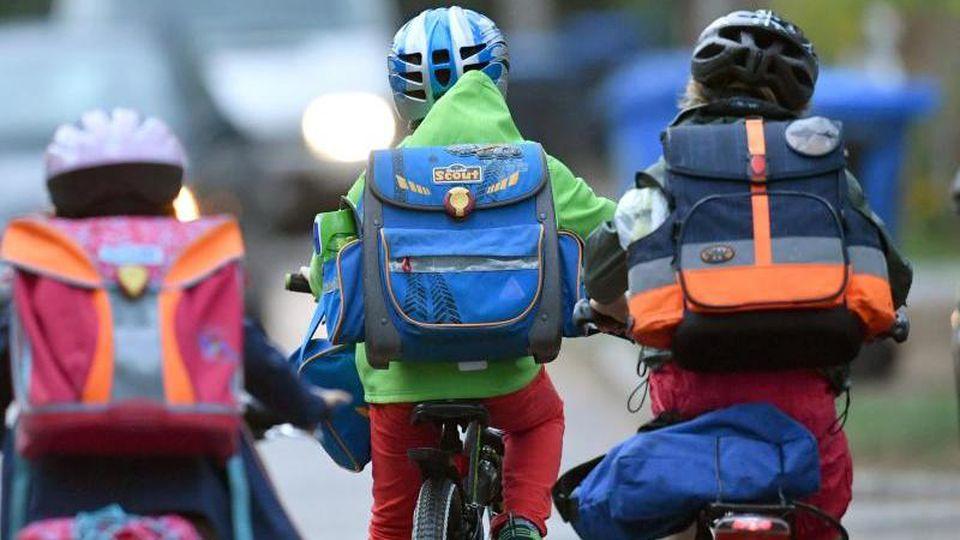 Kinder sind mit dem Fahrrad unterwegs zur Schule. Foto:Ralf Hirschberger/Archivbild
