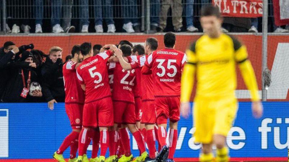 Die Düsseldorfer Spieler (l) freuen sich nach dem Treffer zum 2:0 gegen den BVB. Foto: Marcel Kusch