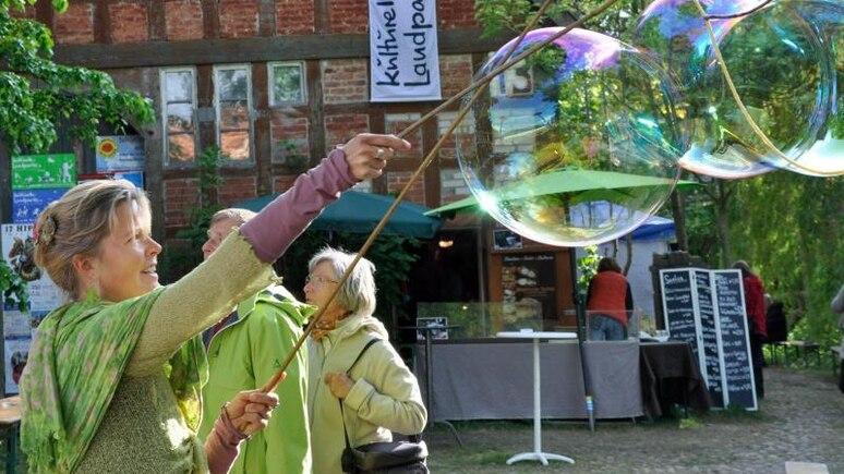 Eine Frau macht im Rahmen der Kulturellen Landpartie ein paar riesige Seifenblasen. Foto: Björn Vogt/dpa/Archivbild