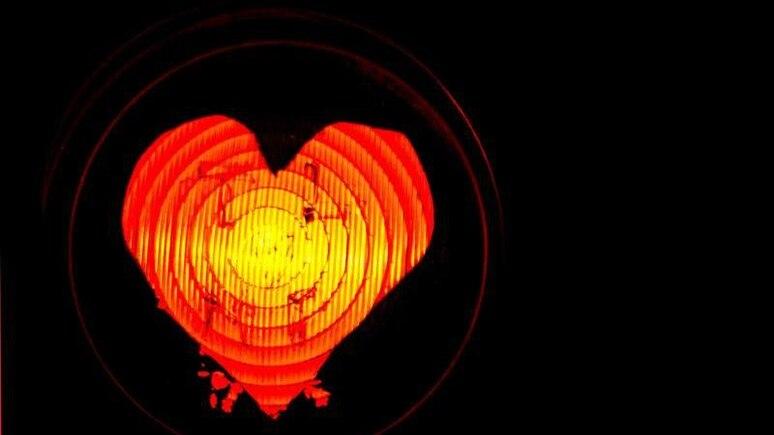 Eine Schablone in Herzform auf einer Radfahrerampel. Foto: Daniel Bockwoldt/dpa/Illustration