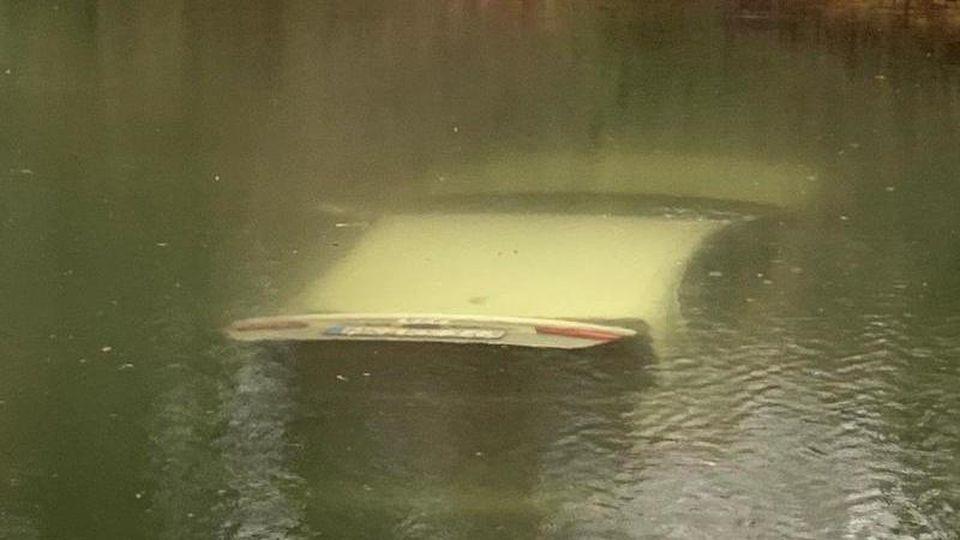 Ein Auto steht mit geöffnetem Kofferraum auf dem Grund eines Teiches. Foto: -/Polizei Märkischer Kreis/dpa