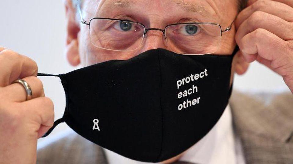 Bodo Ramelow (Die Linke) nimmt vor Beginn der Landtagssitzung seinen Mund-Nasen-Schutz ab. Foto: Martin Schutt/dpa-Zentralbild/dpa