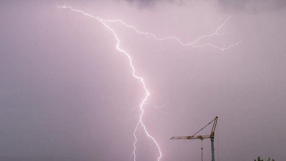 Ein Blitz schlägt am Morgen bei einem Gewitter über einer Landschaft ein. Foto: Julian Stratenschulte/dpa/Symbolbild