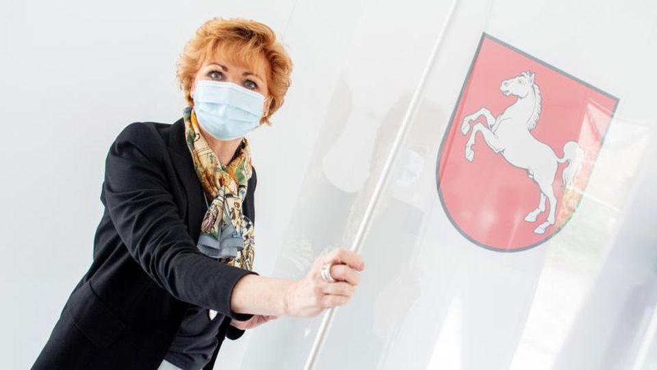 Justizministerin Barbara Havliza (CDU) steht neben dem Landeswappen. Foto: Hauke-Christian Dittrich/dpa/Archivbild