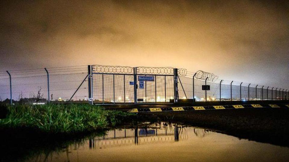 Der Zaun von dem Bremer Flughafen zur Abendstunde. Foto: Mohssen Assanimoghaddam/dpa/Archivbild