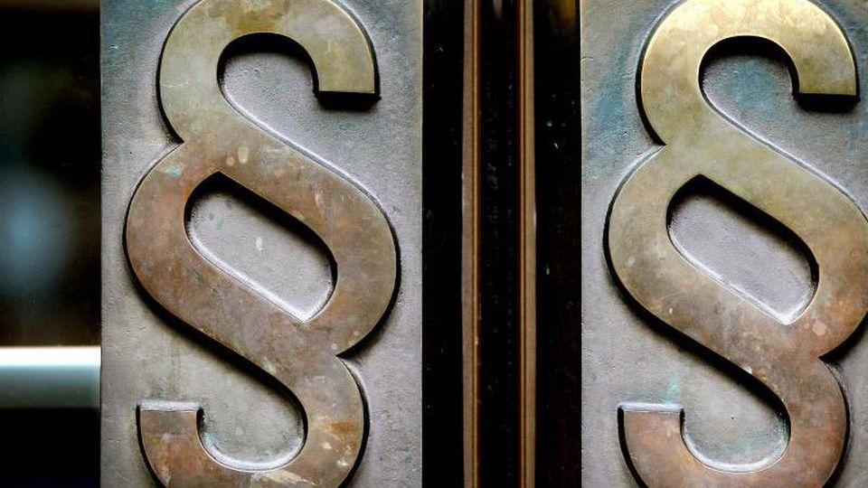 Paragrafen-Symbole sind an Türgriffen angebracht. Foto: Oliver Berg/dpa/Archivbild