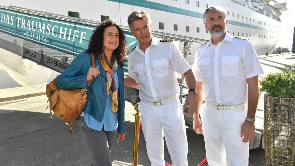 """Hoteldirektorin Hanna Liebhold (Barbara Wussow v.l.n.r.), Dr. Sander (Nick Wilder) und Staff-Kapitän Martin Grimm (Daniel Morgenroth) warten in einer Ausgabe des """"Traumschiff"""" auf neue Gäste."""