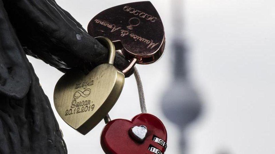 Sogenannte Liebesschlösser hängen an einer Brücke. Foto: Paul Zinken/dpa/Symbolbild