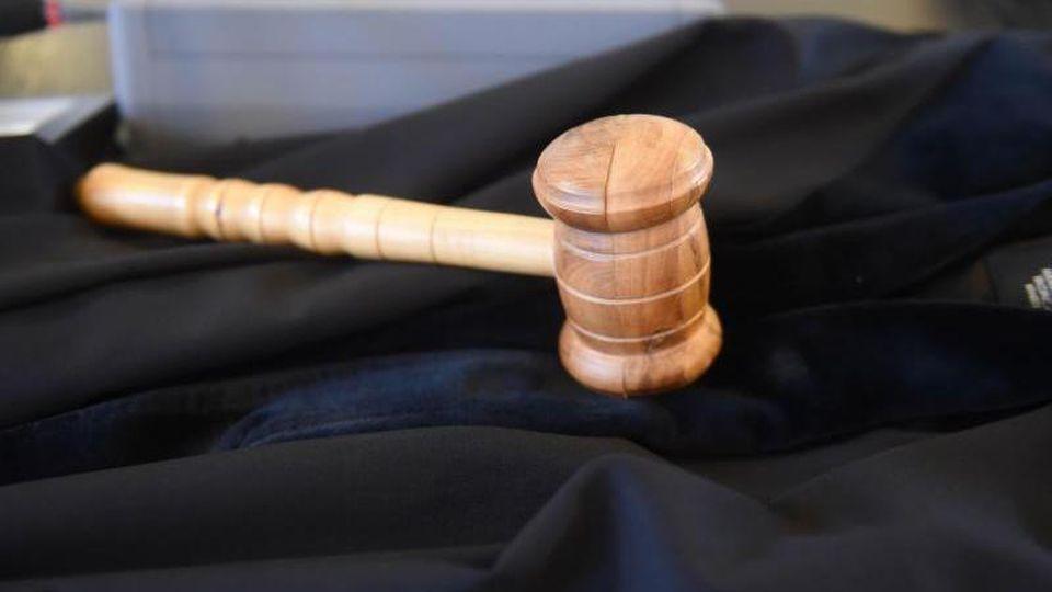 Auf der Richterbank liegt ein Richterhammer aus Holz auf einer Richterrobe. Foto: Uli Deck/Archivbild