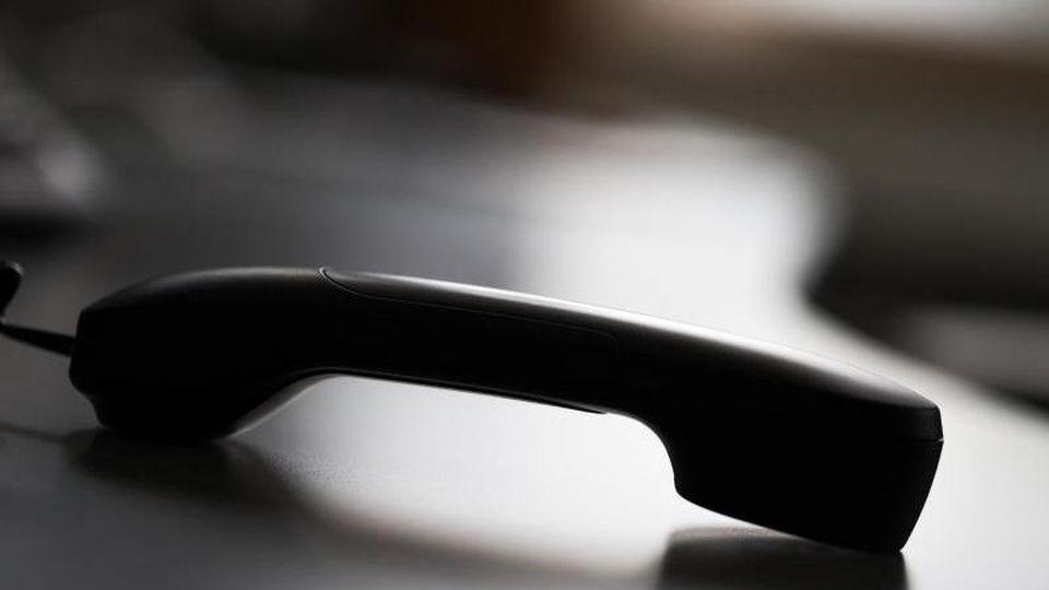 Ein Telefonhörer liegt auf einem Tisch. Foto: Rolf Vennenbernd/dpa/Archivbild