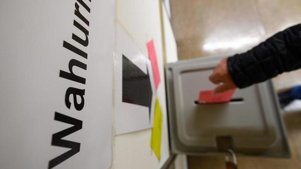 Ein Mann wirft einen Wahlbrief in eine Wahlurne. Foto: Sebastian Gollnow/Archivbild
