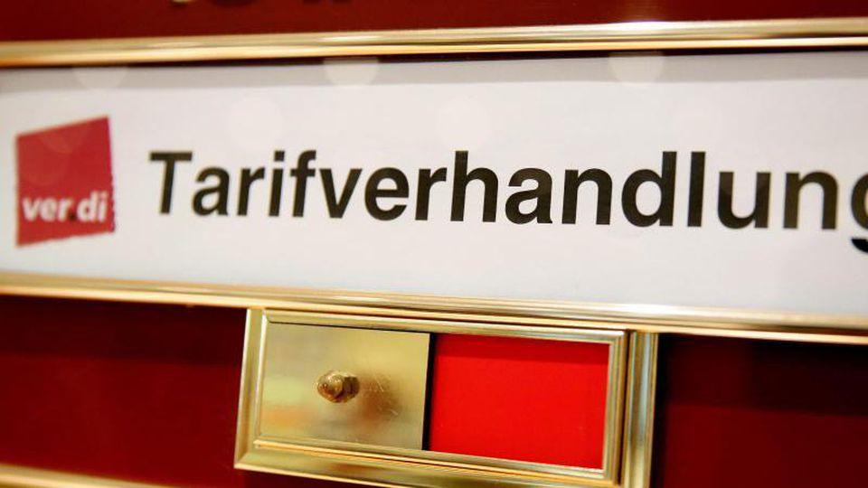 """Ein Schild """"Tarifverhandlungen"""" hängt an einem Konferenzraum in einem Hotel. Foto: Jan Woitas/Archiv"""