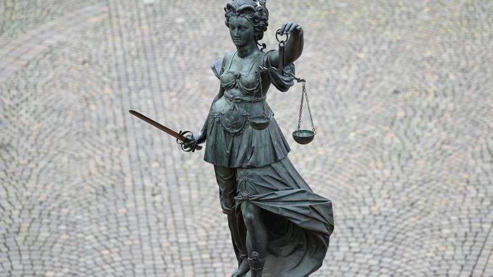 Die Statue der Justitia steht mit einer Waage und einem Schwert in der Hand auf einem Platz. Foto: Arne Dedert/dpa/Archivbild