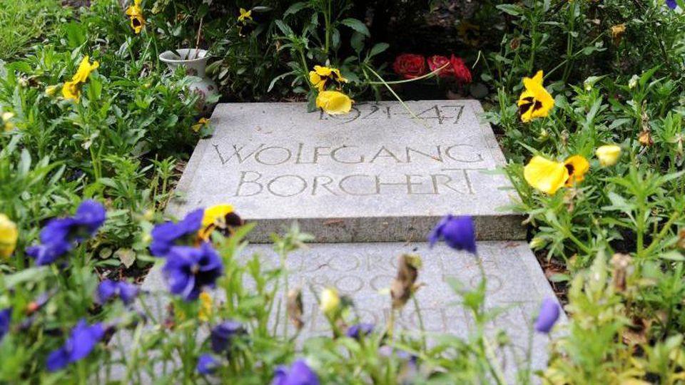 Blumen liegen auf dem Grab des Schriftstellers Wolfgang Borchert (1921-1947) auf dem Friedhof Ohlsdorf in Hamburg. Foto: picture alliance/Maurizio Gambarini/dpa/Archivbild
