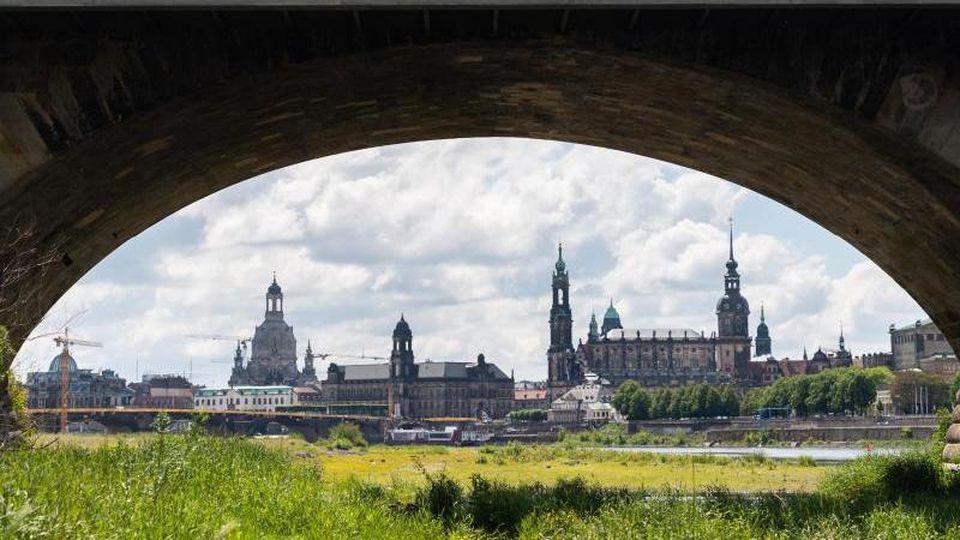Blick durch einen Brückenbogen der Marienbrücke auf die historische Altstadtkulisse an der Elbe. Foto: Robert Michael/dpa-Zentralbild/dpa