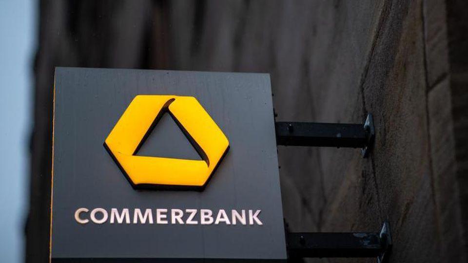 Das Logo der Commerzbank hängt an der Außenfassade einer Filiale. Foto: Daniel Karmann/dpa/Archivbild