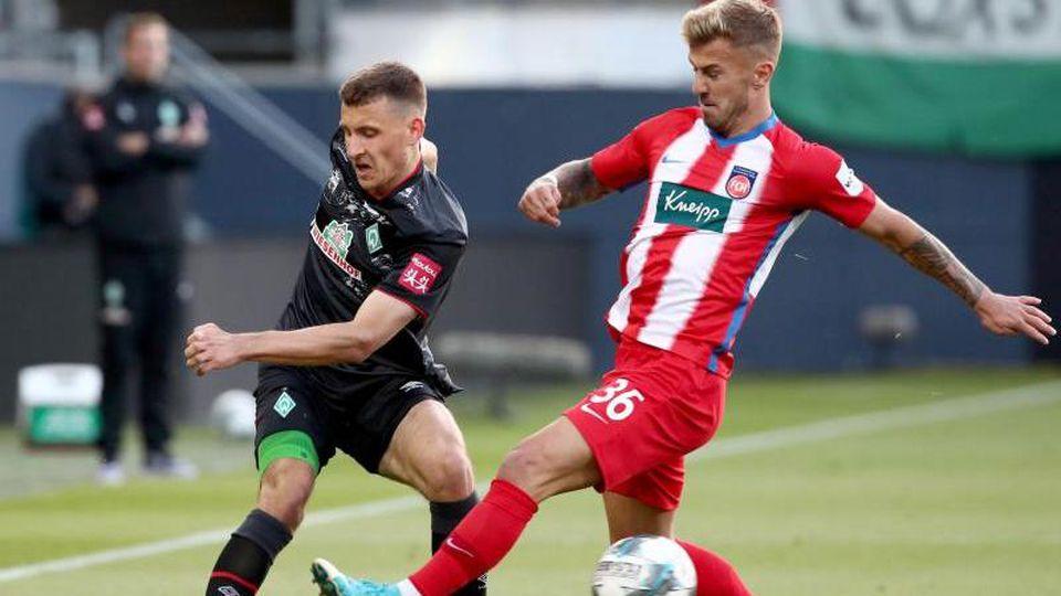 Bremens Maximilian Eggestein und Heidenheims Niklas Dorsch (l-r.) im Zweikampf um den Ball. Foto: Tom Weller/dpa