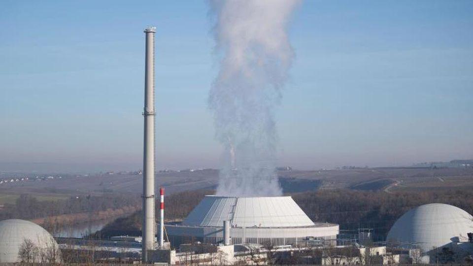 Dampf kommt aus dem Kühlturm (M) von Block 2 des Kernkraftwerks Neckarwestheim. Foto: Marijan Murat/dpa/Archivbild